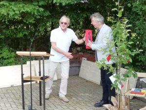 Der Ortbürgermeister überreicht ein Präsent an Pastor Wittmann